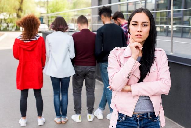 Portrait d'une femme pensive, debout dans la rue