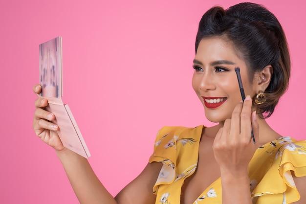 Portrait de femme avec pinceau de maquillage et cosmétique