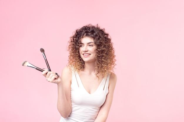 Portrait femme avec pinceaux de maquillage