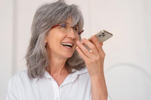 Portrait de femme plus âgée à l'aide d'un appareil smartphone