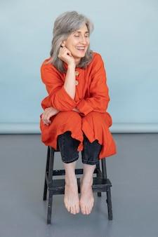 Portrait d'une femme plus âgée élégante posant sur une chaise tout en souriant