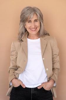 Portrait d'une femme plus âgée élégante posant et étant heureuse