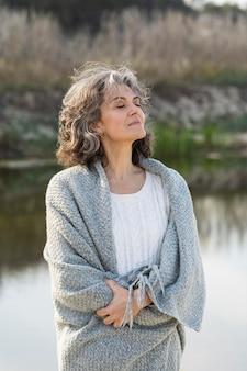 Portrait de femme plus âgée à l'extérieur au bord du lac