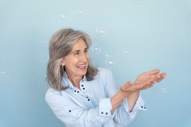 Portrait de femme plus âgée souriante posant tout en jouant avec des bulles