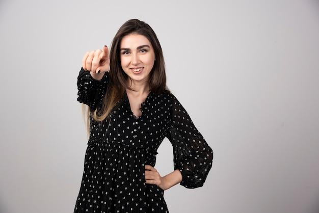 Portrait de femme pointant vers la caméra sur gris.