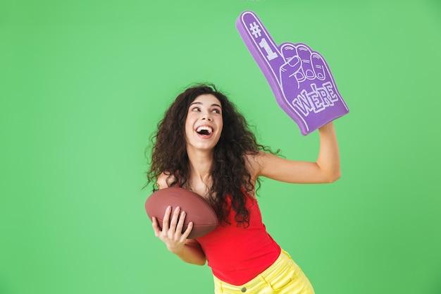 Portrait d'une femme pom-pom girl 20s tenant un gant de fan numéro un et un ballon de rugby en se tenant debout sur un mur vert