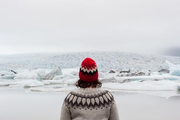 Portrait d'une femme portant un pull islandais devant le lagon de fjallsarlon