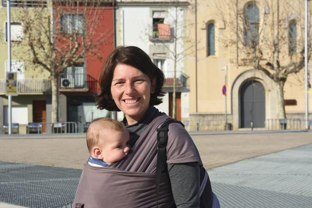 Portrait d'une femme portant son enfant en milieu urbain