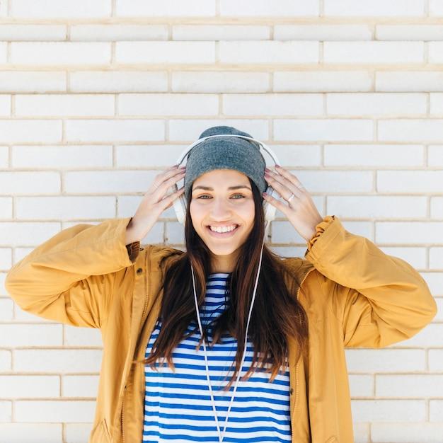 Portrait, femme, porter, chapeau tricoté, et, écouteurs, regarder appareil-photo