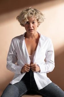 Portrait de femme posant en chemise blanche et montrant son soutien-gorge
