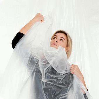 Portrait femme posant avec une feuille de plastique