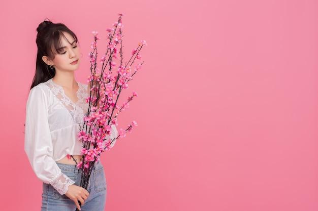 Portrait de femme posant sur fond rose tenant le bouquet à la main.