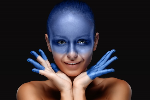 Portrait d'une femme posant recouverte de peinture bleue