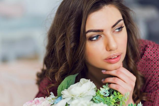 Portrait de femme pose et se détend dans son lit avec des fleurs
