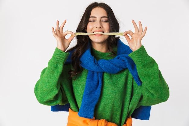 Portrait de femme positive dans des vêtements colorés à mâcher de la gomme longue, debout isolé sur blanc