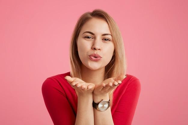 Portrait de femme positive porte un pull rouge et une montre tendance, souffle le baiser en flirtant avec quelqu'un, exprime l'amour et les bons sentiments, isolé sur le mur rose. une femme glamour fait un baiser.