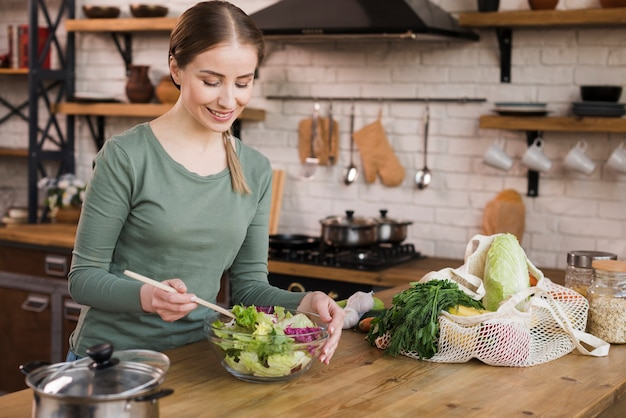 Portrait de femme positive prépare une salade fraîche