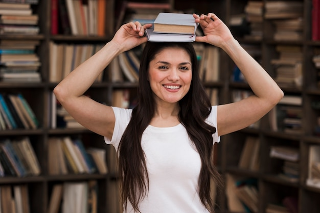 Portrait de femme positive, souriant à la bibliothèque