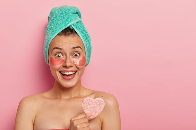 Portrait de femme positive sourit joyeusement, porte des patchs de collagène sous les yeux, tient une éponge cosmétique sur le corps nu, porte une serviette enveloppée