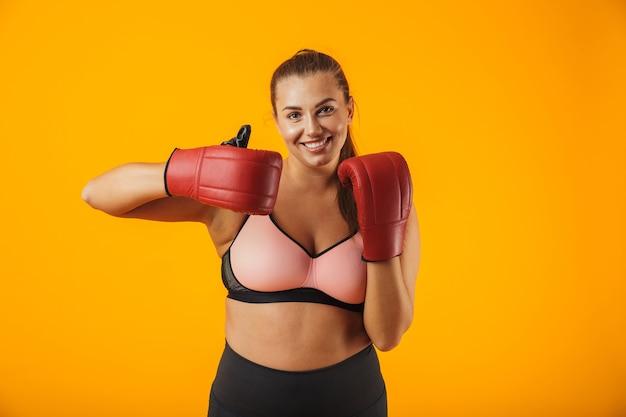 Portrait de femme potelée européenne en soutien-gorge sportif portant des gants de boxe pratiquant, isolé sur fond jaune