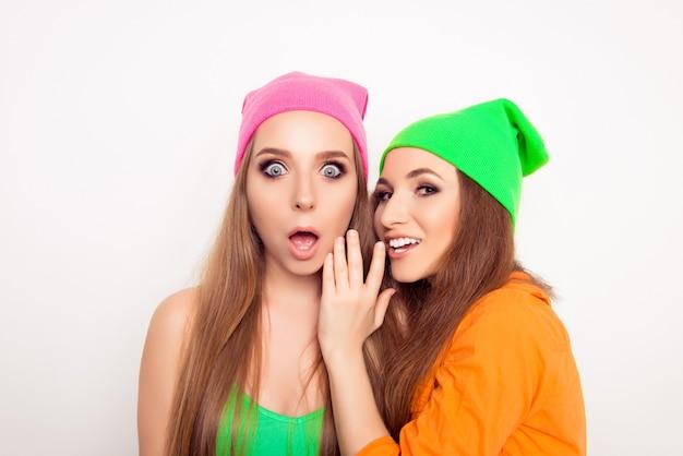 Portrait de femme potins disant des nouvelles à sa petite amie choquée