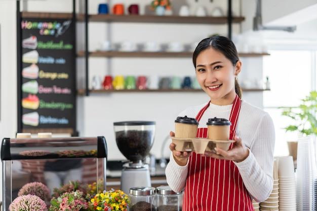 Portrait de femme propriétaire debout à la porte de son café tenant une tasse de café