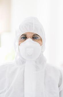 Portrait de femme protégée avec combinaison de sécurité, lunettes et masque avant une pandémie ou un virus