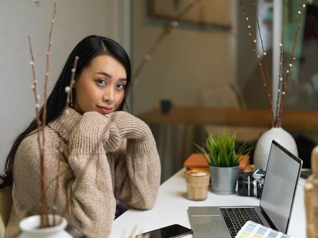 Portrait de femme en pull à l'aide d'un ordinateur portable