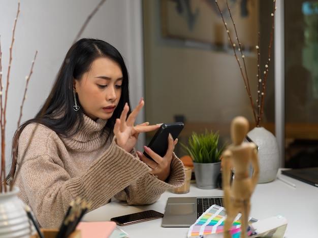 Portrait de femme en pull à l'aide d'un smartphone