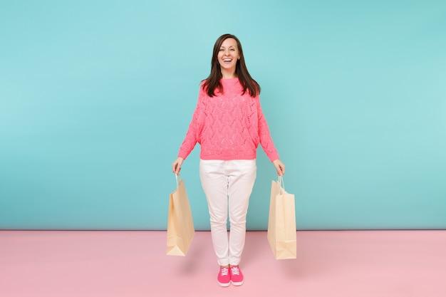 Portrait femme en pull rose tricoté pantalon blanc tenant des sacs de paquets multicolores avec achats