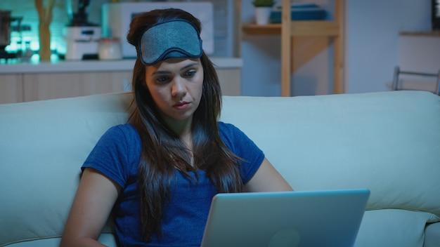 Portrait de femme en pyjama travaillant sur un ordinateur portable tard dans la nuit, assise sur un canapé à la maison. indépendant travaillant devant la télévision, lisant l'écriture, cherchant à naviguer sur un ordinateur portable à l'aide de la technologie internet