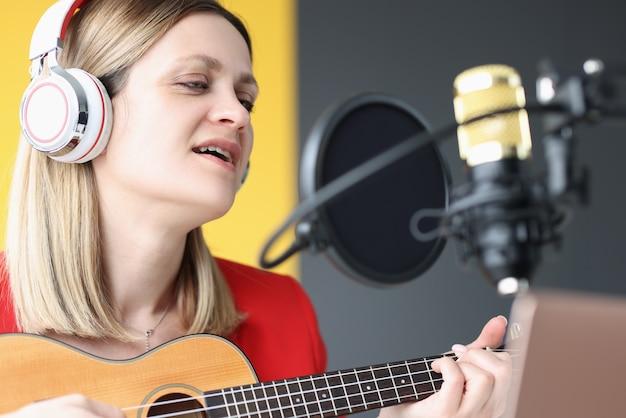 Portrait de femme qui chante dans les écouteurs en face du microphone