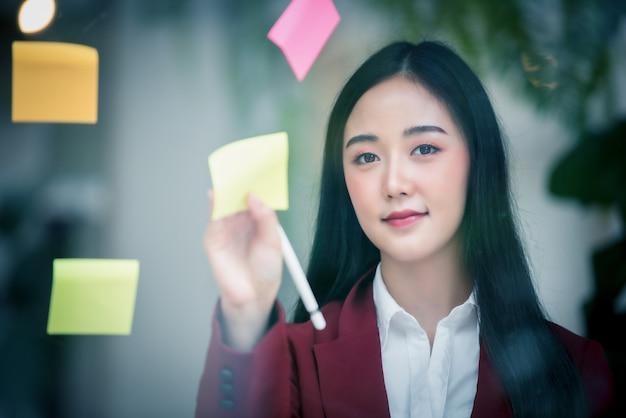 Portrait d'une femme qui écrit sur un bloc de papier collant sur la paroi de verre