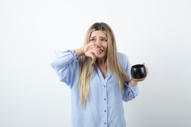 Portrait de femme qui pleure tenant une tasse de boisson chaude avec barre de chocolat