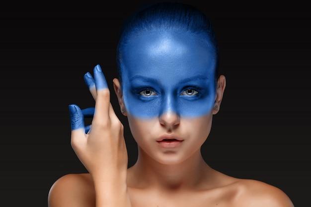 Portrait d'une femme qui pose recouverte de peinture bleue