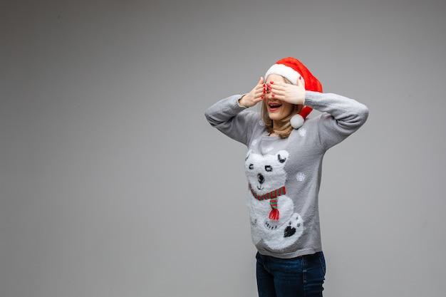 Portrait de femme de race blanche aux cheveux blonds anonyme avec des ongles rouges portant un chandail avec motif d'hiver se cachant les yeux tout en posant sur le sol avec des confettis colorés