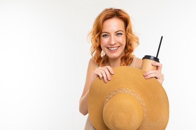 Portrait de femme de race blanche aux cheveux roux, joli visage en belle robe légère et grand chapeau sourit et boit du café