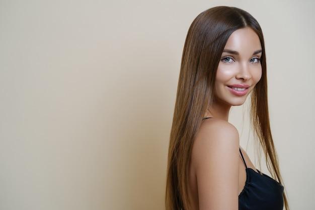 Portrait de femme ravie heureuse aux longs cheveux noirs, sourit doucement