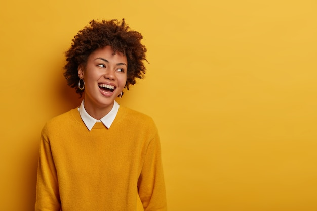 Portrait de femme ravie à la recherche agréable rit et détourne le regard