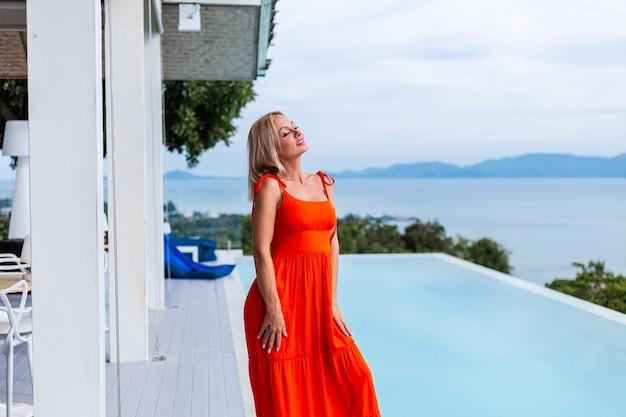 Portrait de femme à la recherche de luxe en robe de soirée orange rouge dans un hôtel riche