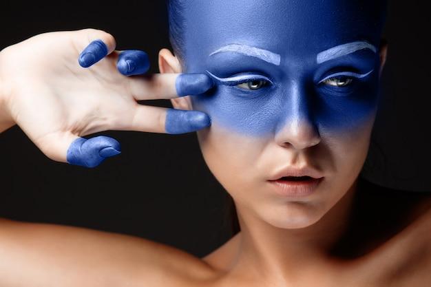 Portrait d'une femme recouverte de maquillage artistique bleu