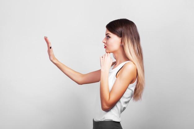 Portrait de femme réfléchie assez confiante, debout sur un mur gris avec copie espace