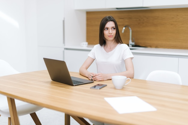 Portrait d'une femme réfléchie assise à table et regardant loin. fille travaillant à la maison. la femme regarde loin alors qu'elle était assise au bureau. tasse de café blanche, feuille de papier vierge et téléphone sur table