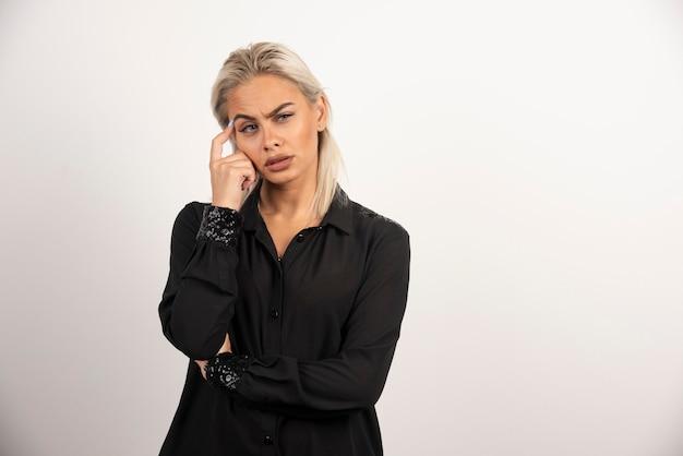 Portrait de femme réfléchie en chemise noire posant sur fond blanc. photo de haute qualité