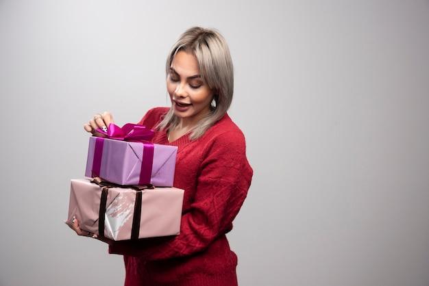 Portrait de femme regardant les coffrets cadeaux sur fond gris.