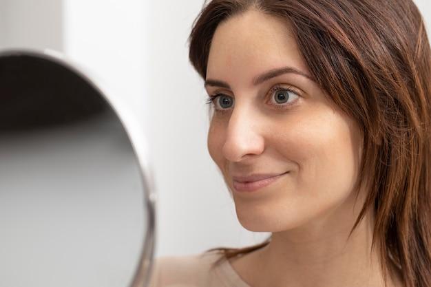 Portrait de femme regardant dans le miroir après son traitement de microblading