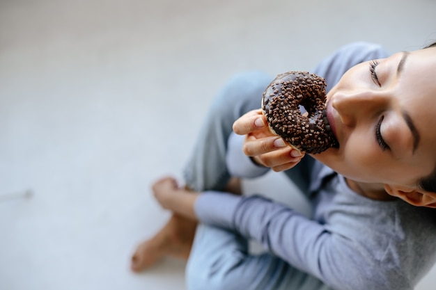 Portrait de femme réjouissante mange de délicieux beignets à la maison.