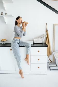 Portrait de femme réjouissante mange un délicieux croissant à la maison. concept de nourriture malsaine.