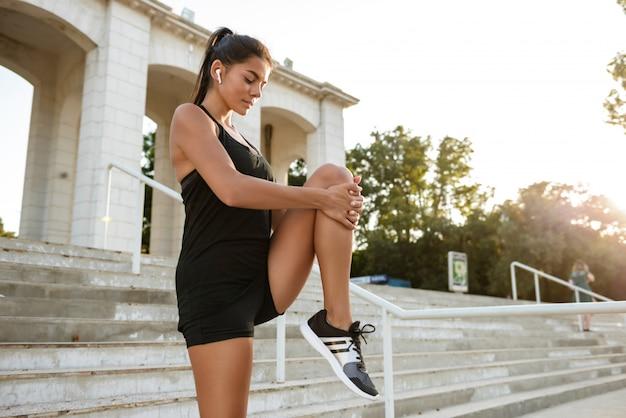 Portrait d'une femme de remise en forme dans les écouteurs qui s'étend de ses jambes