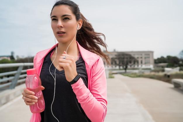 Portrait d'une femme de remise en forme qui court à l'extérieur dans la rue. concept de sport et de mode de vie sain.